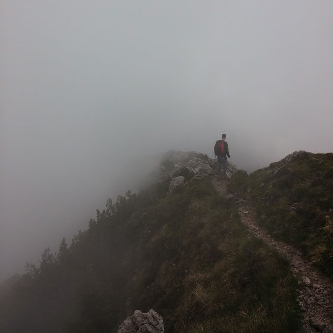 Person hiking into heavy fog