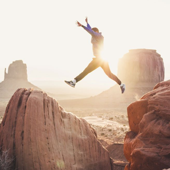 Person leaping between rocks