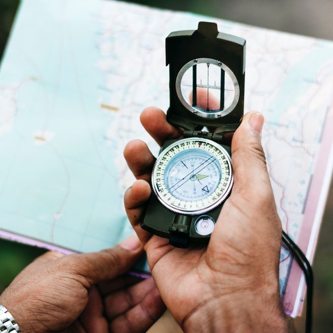 Person holding map and compass